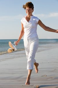 Active and happy senior woman running at the beach
