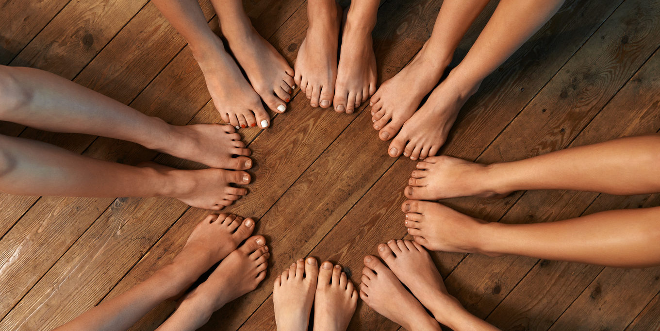 feet of dancers seated circle on the floor